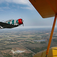 Off the yellow wings of a 1941 Stearman Biplane, Times staff writer Chuin-Wei Yap can be seen in the front seat of the cockpit of a 1955 T-6 Texan as pilot John Mackinson takes him for an aerobatic thrill ride above Zephyrhills Friday morning. The experience is part of the 2008 Barnstormer Tour by History Flight, and offers a variety of packages for a flight experience in a restored WWII aircraft..BRENDAN FITTERER   Times
