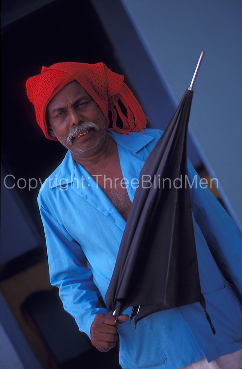 Man with a black umbrella, gold tooth and red turban plus blue shirt!
