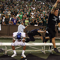 Boise State receiver Jeremy Childs sits on the Boise State bench moments after time ran out, as a Honolulu police officer tries to keep a fan from storming the field after the Warriors' victory at Aloha Stadium in Honolulu, HI. The win clinched a Western Athletic Conference Title for Hawaii.
