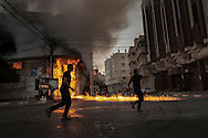 Gaza Strip, Gaza City: Palestinians run in front of a soap factory in Gaza City right after was hit by an Israeli airstrike on August 10, 2012. ALESSIO ROMENZI