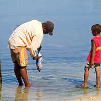 A man shows his boy how to clean a tuna fish on the Caribbean island of Roatan, Honduras.