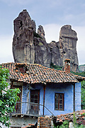 """Fantastic rock spires of Meteora rise above a blue house with red tile roof in Kastraki, near Kalambaka, in central Greece, Europe. Meteora (which means """"suspended in the air"""") is a complex of six Eastern Orthodox Christian monasteries built by medieval monks on natural rock pillars near Kalambaka, in central Greece, Europe. The sandstone and conglomerate of Meteora were formed in the cone of a river delta estuary emerging into a sea about 60 million years ago, then later uplifted and eroded into pinnacles. The isolated monasteries of Meteora helped keep alive Greek Orthodox religious traditions and Hellenic culture during the turbulent Middle Ages and Ottoman Turk occupation of Greece (1453-1829). UNESCO honored Meteora as a World Heritage Site in 1988. Visit early in the morning and in the off season to avoid crowds. Published in """"Light Travel: Photography on the Go"""" book by Tom Dempsey 2009, 2010."""
