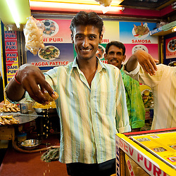 A vendor at a food stall on Juhu Chowpati beach serving dripping Pani Puri. Mumbai, August 2009