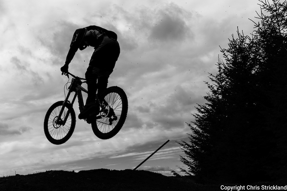 Ae Forest, Dumfries, Scotland, UK. 25th April 2015. A Downhill Mountain Bikers jumps off a feature on the 7Stanes course at Ae during the Scottish Downhill Association racing.