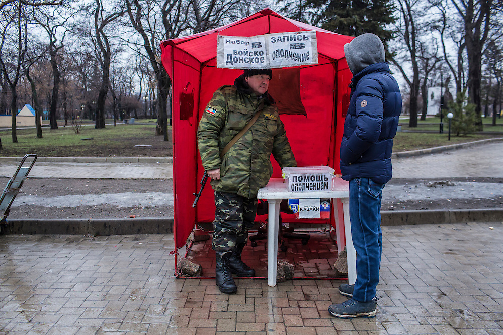 DONETSK, UKRAINE - FEBRUARY 2, 2015: A recruiter for rebel fighters who goes by the nickname Kot, left, gives information to Spartak Chavelashvili, right, who was signing up to fight against Ukrainian forces in Donetsk, Ukraine. Donetsk leader Aleksandr Zakharchenko announced today that rebels plan to mobilize a total of 100,000 fighters in ten days for an ongoing offensive against Ukraine. CREDIT: Brendan Hoffman for The New York Times