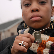 Date: 12/1/06<br /> desk: metro<br /> slug: dorismond<br /> id: 30034277A<br /> <br /> Mourner Anne Victor, 24, holds up a charm listing the date of her 1995 middle school anniversary with Sean Bell, as she leaves his wake at the Community Church of Christ in Queens, New York on December 1, 2006. They dated when they were 8th grade students at Parsons 168 public school in New York City and he gave her this gift. Bell, 23, was killed in a hail of 50 bullets by New York City police officers in the early morning of November 25, 2006 leaving his bachelor party at Club Kalua in Queens, just hours before he as scheduled to marry in the church where his funeral was held.<br /> <br /> photo by Angela Jimenez for The New York Times<br /> photographer contact 917-586-0916