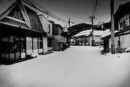 Nuclear winter in Fukushima, Prefecture: Main business district of evacuated village in the extended nuclear evacuation zone where no one, not even the police, have passed since this heavy snow storm started, Tsushima, Fukushima Prefecture, Japan.  Tsushima residents were forced to evacuate their village after a wind-driven radioactive cloud from an explosion at Fukushima Dai Ichi nuclear power plant scored a direct hit on this valley.  Estimated annual radiation levels exceed 50 millisieverts, making the village unihabitable for years, maybe even decades as Tsushima is one of most irradiated villages in Fukushima Prefecture.
