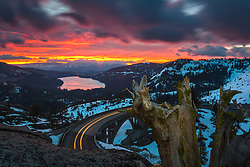 """Donner Lake Sunrise 13"" - Photograph of a vibrant sunrise above Donner Lake and Rainbow Bridge with a old dead stump in the foreground."