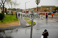 MANENBERG, SOUTH AFRICA - SEPTEMBER 15: Residents walk down the street after a rain storm on a Sunday morning on September 15, 2013 in Manenberg, a township of Cape Town, South Africa. In August, 16 schools were closed in the area due to increasing gang violence. An uncertain peace has been brokered between the gangs to help the community resume their daily lives. Photo by Ann Hermes/The Christian Science Monitor