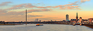 A view of downtown Duesseldorf with the ancient tower, the Rhine river and the railways bridge at sunset. Taken a few minutes before sunset, this is stitched from nine vertical frames