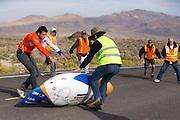 De VeloX4 komt net ten val bij het stoppen van de fiets. Het Human Power Team Delft en Amsterdam (HPT), dat bestaat uit studenten van de TU Delft en de VU Amsterdam, is in Amerika om te proberen het record snelfietsen te verbreken. Momenteel zijn zij recordhouder, in 2013 reed Sebastiaan Bowier 133,78 km/h in de VeloX3. In Battle Mountain (Nevada) wordt ieder jaar de World Human Powered Speed Challenge gehouden. Tijdens deze wedstrijd wordt geprobeerd zo hard mogelijk te fietsen op pure menskracht. Ze halen snelheden tot 133 km/h. De deelnemers bestaan zowel uit teams van universiteiten als uit hobbyisten. Met de gestroomlijnde fietsen willen ze laten zien wat mogelijk is met menskracht. De speciale ligfietsen kunnen gezien worden als de Formule 1 van het fietsen. De kennis die wordt opgedaan wordt ook gebruikt om duurzaam vervoer verder te ontwikkelen.<br /> <br /> The VeloX4 falls at the finish. The Human Power Team Delft and Amsterdam, a team by students of the TU Delft and the VU Amsterdam, is in America to set a new  world record speed cycling. In 2013 the team broke the record, Sebastiaan Bowier rode 133,78 km/h (83,13 mph) with the VeloX3. In Battle Mountain (Nevada) each year the World Human Powered Speed Challenge is held. During this race they try to ride on pure manpower as hard as possible. Speeds up to 133 km/h are reached. The participants consist of both teams from universities and from hobbyists. With the sleek bikes they want to show what is possible with human power. The special recumbent bicycles can be seen as the Formula 1 of the bicycle. The knowledge gained is also used to develop sustainable transport.