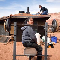 032713       Brian Leddy<br /> Bessie Wilson sits on a weight bench in her yard as Doug Vilsack installs a small solar panel on her hogan near Cedar Ridge, Ariz, Wednesday, March 27.
