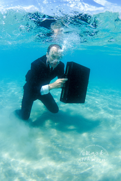 Businessman in ocean with briefcase