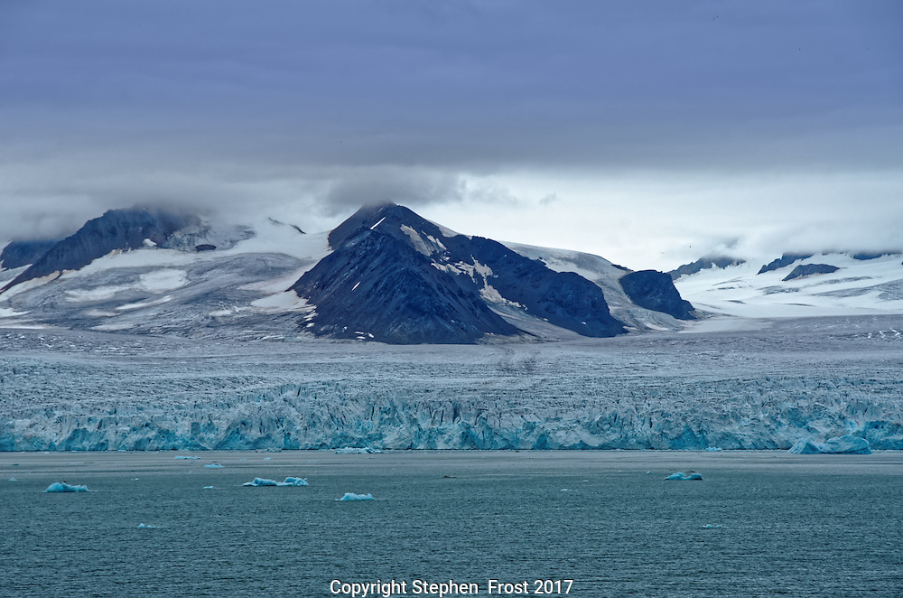 Glacier in Svalbard, with small floating icebergs.<br /> <br /> Svalbard, formerly known as Spitsbergen, is a Norwegian Archipelago in the Arctic Ocean.