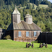 """Originally built in the 1820s, the restored chapel at Fort Ross was the first Russian Orthodox structure in North America outside of Alaska. Fort Ross State Historic Park preserves a former Russian colony (1812-1842) on the west coast of North America, in what is now Sonoma County, California, USA. The 5.5-inch howitzer cannons are historical reproductions. Visit Fort Ross and dramatic coastal scenery 11 miles north of Jenner on California Highway One. For centuries before Europeans arrived, this site was called Metini and had been occupied by the Kashaya band of Pomo people who wove intricate baskets and harvested sea life, plants, acorns, deer, and small mammals. Sponsored by the Russian Empire, """"Settlement Ross"""" was multicultural, built mostly by Alaskan Alutiiq natives and occupied by a few Russians plus 300-400 native Siberians, Alaskans, Hawaiians, Californians, and mixed Europeans. Initially, sea otter pelts funded Russian expansion, but by 1820, overhunting motivated the Russian-American Company to introduce moratoriums on hunting seals and otters, the first marine-mammal conservation laws in the Pacific. Russian voyages greatly expanded California's scientific knowledge. Renamed """"Ross"""" in 1812 in honor of Imperial Russian (Rossiia), Fortress Ross was intended to grow wheat and other crops to feed Russians living in Alaska, but after 30 years was found to be unsustainable. Fort Ross was sold to John Sutter in 1841, and his trusted assistant John Bidwell transported its hardware and animals to Sutter's Fort in the Sacramento Valley. Fort Ross is a landmark in European imperialism, which brought Spanish expanding west across the Atlantic Ocean and Russians spreading east across Siberia and the Pacific Ocean. In the early 1800s, Russians coming from the north met Spanish coming from the south along the Pacific Coast of California, followed by the USA arriving from the east in 1846 for the Mexican-American War. Today, Fort Ross is a California Historical Landmar"""