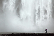 The waterfalls of Skógafoss in Southern Iceland mark the previous extent of the country's cliffs, but the coastline has receded seaward. Even in the fog and rain it is popular with tourists.