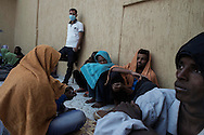 Libya, Garabulli: At Alguaiha detention center Somali migrants captured at the sea as they were attempting to reach Italy seat in the courtyard of the facility as a Libyan guard stands nearby them on May 12, 2015. Alessio Romenzi