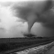 "A tornado sweeps across rural Kansas in 1977.  Kansas is one of a handful of states that lies in ""Tornado Alley""."