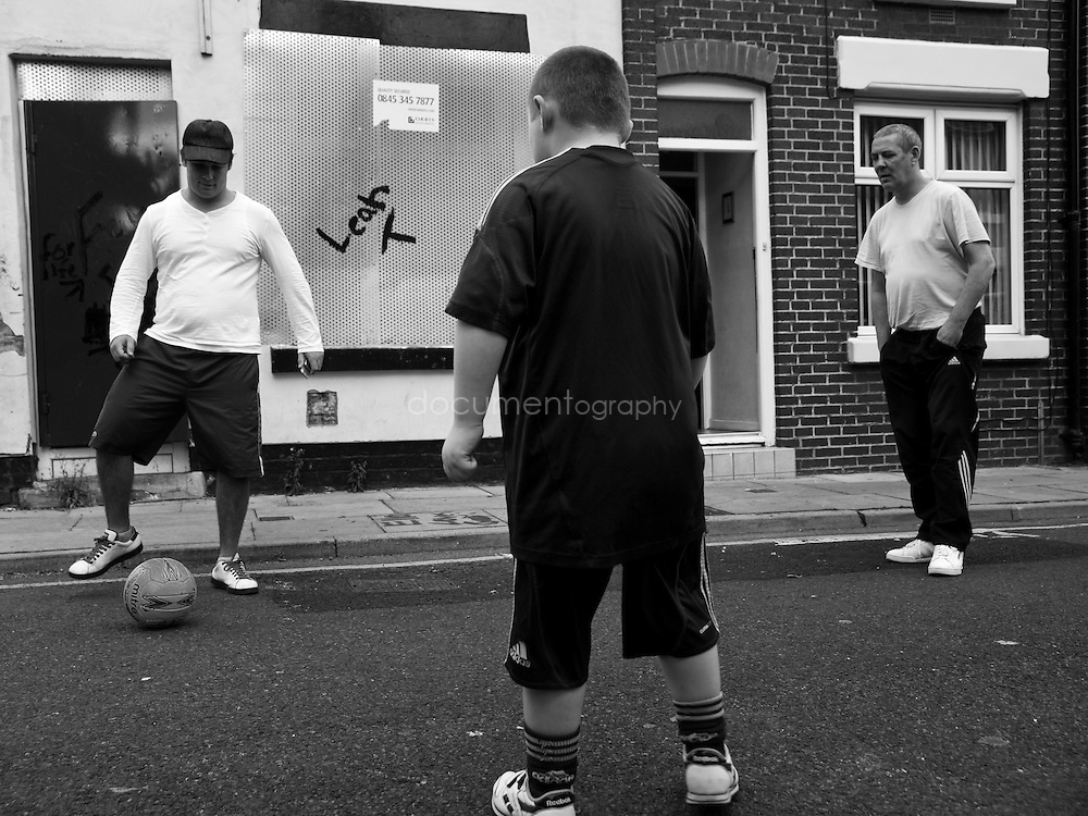 Some of the last remaining resident of Anfield Paul Turton and his father (back) play football with a Connor Thompson, their neighbour...OLYMPUS DIGITAL CAMERA