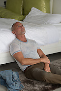 mature man at home in deep thought while sitting on the floor and leaning on a bed