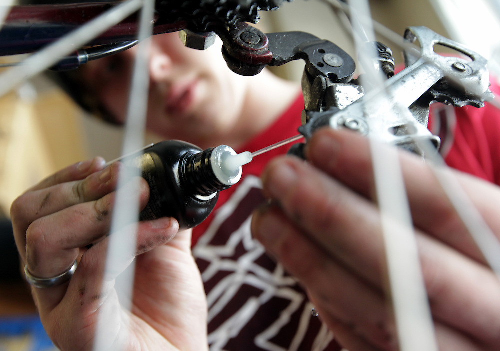 Ty Spangle, 17, makes adjustments on a refurbished bicycle at Express Bike Shop in St. Paul, Minnesota.  Formerly a Youth Express apprentice, Spangle is now a mechanic at the shop, teaching skills to new program participants..