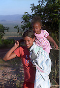 Woman of Kalunga quilombo (maroon community, community formed by fugitive slaves) carrying child. The Kalunga community consist of 5 villages spread in a moutainous region in northern Goiás, Brazilian Highlands.