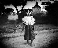 "Young Burmese girl, her face painted with ""thanaka"" sun screen made from tree bark, at dusk in the Bagan temple complex, Burma."