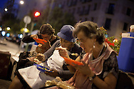 (L-R) Antonia Sastre Castilla 45, her mother Carmen Castilla 77, and her sister Carmen Aurora 49 eat salad for dinner in the street on September 3, 2012, in Madrid, Spain. The family of four were evicted from the flat they were renting on April 24th, after Rosa lost her job and the main income of the family. They couldn't afford to pay anymore their rent. Social Services provided with temporally shelter for 15 days, but after that they found themselves living in the street. They have wrote to the Spanish Prime Minister, the King, the Prince and the Queen of Spain, the President of Madrid but all answers received were saying that they were really sorry about their situation but there was nothing they could do on their hands, referring them to the Social Services. They have registered their census in a piece of street of Madrid. Neighbors often give them a hand providing food, blankets, charging mobiles or making their laundry. The family lives of their mother's widow's pension, some money they get from visually impaired Antonia's welfare allowance, and whatever income the sister Carmen Aurora can get working as a concierge at a nearby building.They sleep rough in a store front door nearby. Carmen 77, with back and heart problems, sleeps sitting on her armchair as she is not able to stand up from ground level if she would sleep on top of a mattress.