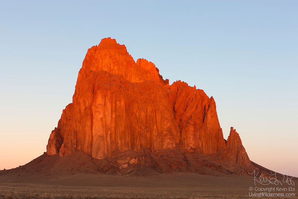 """Shiprock, a prominent peak located northwestern New Mexico, is turned golden at sunrise. The peak rises 1,583 ft (482 m) above the surrounding landscape and has a total elevation of 7,177 ft (2,188 m). The peak is located on Navajo tribal land and is sacred to them. The Navajo name for the peak is Tsé Bit'a'í, which means """"rock with wings."""" Tribal legend says a great bird brought the Navajo people from the North to the present-day Four Corners area."""
