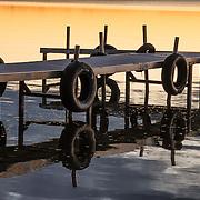 Dock reflects in Lake Mitchell at sunset, at Lakeside Charlies restaurant, near Sun-N-Snow Motel, Cadillac, Michigan, USA.