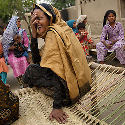 Mukhtar Mai, 33, laughs with relatives during a visit her to aunts house, whom she hadn't seen in four years, Meerwala, Pakistan, April 28, 2005. Mai, went against the Pakistani tradition of committing suicide when she brought charges against the men who gang raped her nearly three years ago.