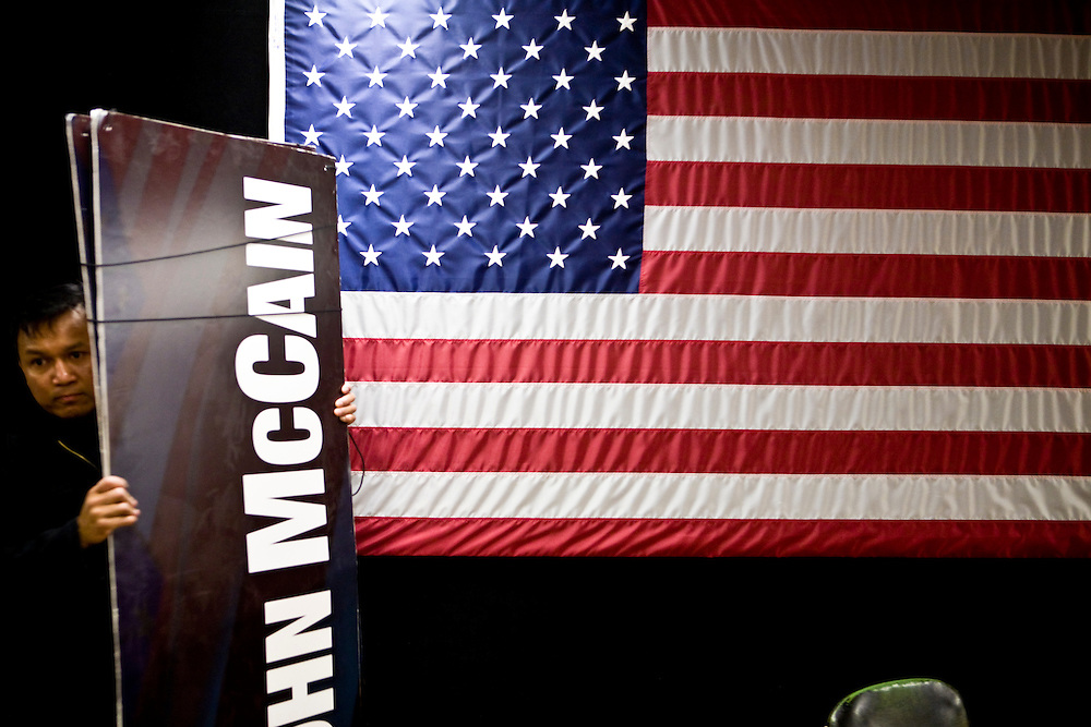 A volunteer carries a sign at a town hall meeting with Sen. John McCain (R-AZ) in Laconia, NH, on Tuesday, Jan. 1, 2008.