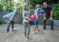 """""""We love family dodgeball...girls against the boys.  The boys beat up on us...they show no mercy.  Someday we will be victorious!""""  -Genevieve Welsh with her husband, Thomas Brown, and children, Hazel (7) and Oscar (9), in the driveway of their home on Cedar Street in Calistoga."""