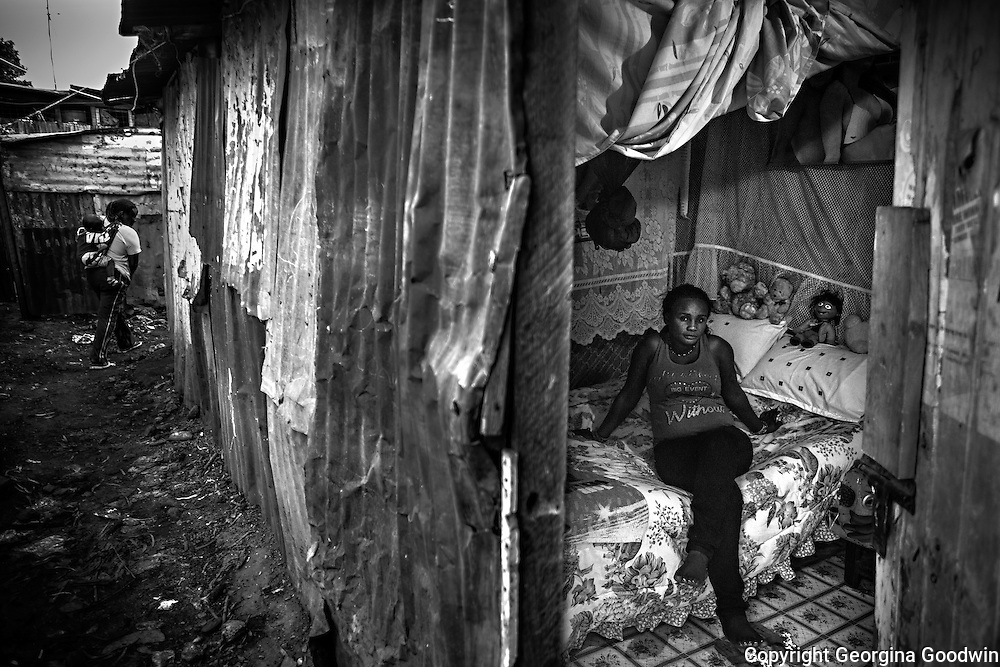 Priscilla, aged 26, in her rented room in Mugumoini Village slum. Raped  by 2 men on her way home one night after a party with friends she was left abandoned on the roadside, drunk and naked. A woman from the Kenya Wildlife Service found her the next day and took her home. She has continuous health problems as a result forcing her to make regular visits to the local community health centre. She has been an inspiration to other raped women in the community and continues to come forward.<br /> This image is from a series focusing on and around the rape and the women victims that occur every half a day in Mugumoini Village in Nairobi's Southlands, a slum home to 20,000 people in abject poverty with little or no income, with the aim of creating exposure and empowerment for change. &copy;GGoodwin