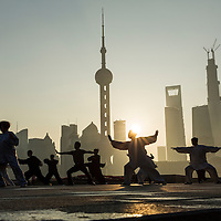 Peoples Republic of China, Shanghai, Silhouette of martial arts group practicing along Huangpu River promenade beneath Pudong skyline at dawn