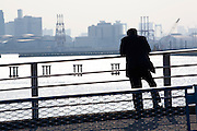 Man smoking while viewing an industrial area of Tokyo bay near Shin Kiba