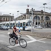 Bicyclist & tram by main train station in Zurich, Switzerland, Europe.