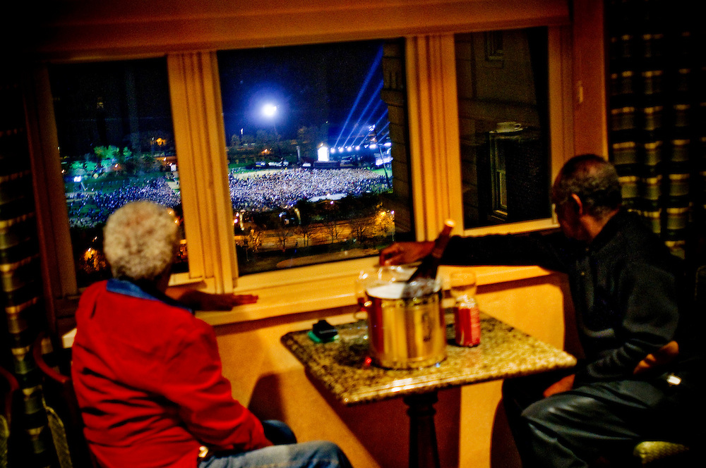 "Obama Election Night in Grant Park, Chicago..Dorothy and James Jackson from Oak Park, Il,  watching from a window at the Hilton Chicago, overlooking the crowds waiting for Obamas victory speech in Grant Park. Mr Jackson says ""It's beautiful. That's all I can say. I never dreamed I would see it""....Chris Maluszynski /Moment / Agence VU"