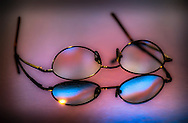 Wire rimmed glasses sitting on the counter with beautiful colored light from outside reflected.