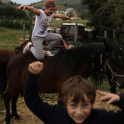 Ginevra, 10, and her brother Giulio Cesare, 7, play with their horses in the family's farm in the town of Santo Stefano di Sessanio in the province of L'Aquila in Abruzzo.