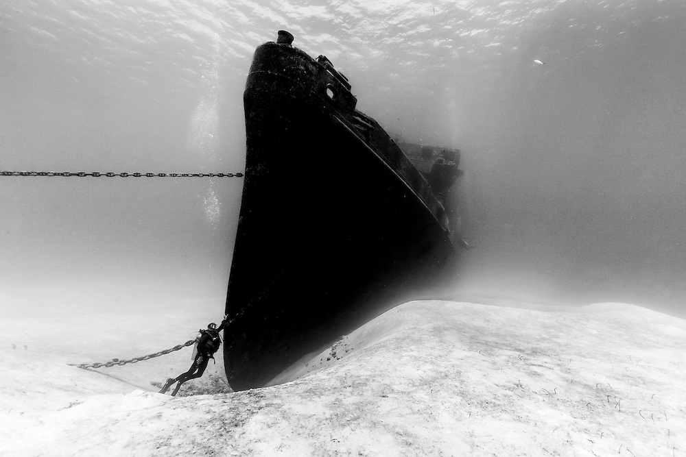 Caribbean, Grand Cayman. Wide angle view of the USS Kittiwake with a diver on the bow.
