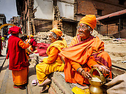 04 MARCH 2017 - KATHMANDU, NEPAL: Hindu women who live as religious ascetics sit on the wall around a temple destroyed in the 2015 earthquake. Recovery seems to have barely begun nearly two years after the earthquake of 25 April 2015 that devastated Nepal. In some villages in the Kathmandu valley workers are working by hand to remove ruble and dig out destroyed buildings. About 9,000 people were killed and another 22,000 injured by the earthquake. The epicenter of the earthquake was east of the Gorka district.     PHOTO BY JACK KURTZ