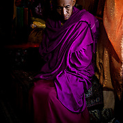 A Buddhist monk sits in the window light in a monastery.