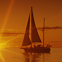 Yacht silhouette on orange sea with setting sun