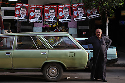 A man stands in front of a string of campaign posters for Mohamed Morsi.