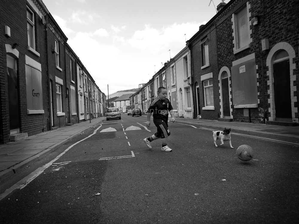 Connor Thompson plays football in his deserted street with the Liverpool FC Stadium in the background...OLYMPUS DIGITAL CAMERA