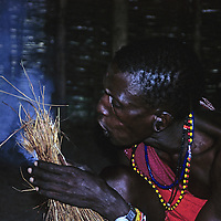 Africa, Kenya, Maasai Mara. Maasai tribesman demonstrates fire starting with grass.