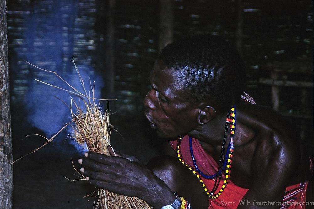 Africa, Kenya, Maasai Mara. Maasai tribesman demonstrates fire starting with grass.