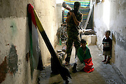 Palestinian resistance fighter Abu Jandal with his sons Mustafa,4, and Issa,7, in storage shack at their home where he is keeping two Qassam rockets and and three tank mines in hiding July 1,2006 in Beit Hanoun in the Gaza Strip. Abu Jandal said that the weapons are moved every three hours and sometimes they are even kept in the sleeping room of his 7th month old son .(Photo By Heidi Levine/Sipa Press).