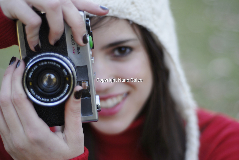 MR Portrait of a cute and sweet spanish teenager girl playing with an old camera, in the park